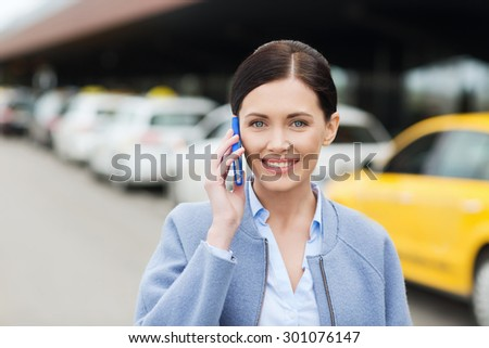 travel, business trip, people and tourism concept - smiling young woman calling and talking on smartphone over taxi station or city street - stock photo