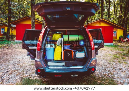 Travel car and camping luggage packed in the full car trunk. Outdoor wanderlust items. Outdoor, adventures and travel suv. Ready to go concept. Vintage hipster tone. Camping exploring. - stock photo