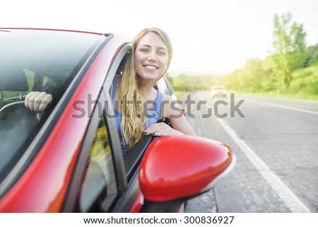 Travel concept. Attractive smiling girl in a red car. At sunset.  - stock photo