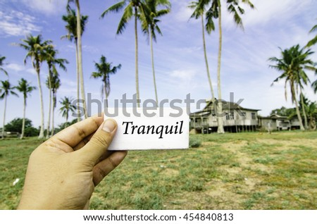 travel concept, cropped hand holding white canvas with word tranquil guide over blurred background of rural area.wooden house surrounded by coconut tree at sunny day and cloudy blue sky - stock photo