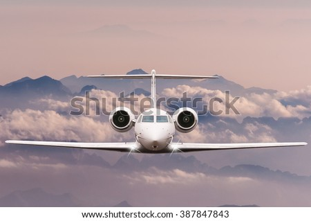 Travel concept. Front view of Jet airliner in flight with sky, cloud and mountain background. Commercial passenger or cargo aircraft, business jet fly over Alps.  - stock photo