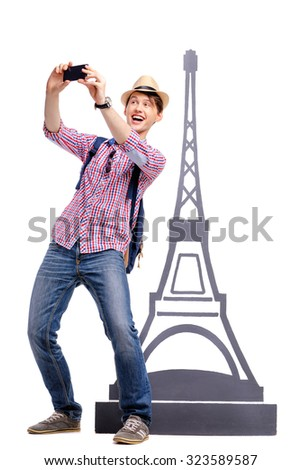 Travel concept. Full length studio portrait of handsome young man taking selfie near eifel tower. Isolated on white. - stock photo