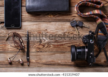 Travel concept - headphones, camera,  sketchbook, purse, pencil and keys on wooden background. - stock photo
