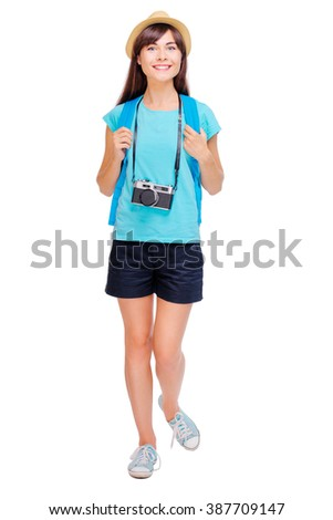 Travel concept. Studio portrait of pretty young woman in hat with backpack. Isolated on white. - stock photo
