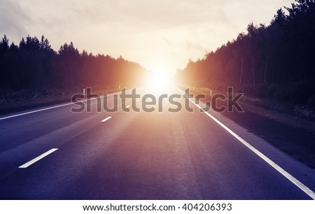 travel concept, sunrise on an empty road - stock photo