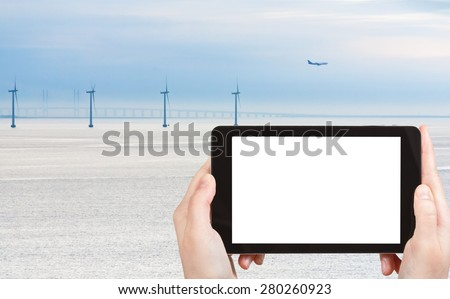 travel concept - tourist photograph Middelgrunden offshore wind farm and oresund bridge near Copenhagen, Denmark on tablet pc with cut out screen with blank place for advertising logo - stock photo
