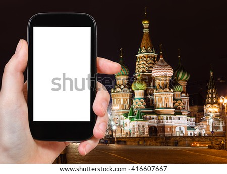 travel concept - tourist photographs Moscow night landscape with Kremlin Pokrovskiy Cathedral on Red Square on smartphone with cut out screen with blank place for advertising, Russia - stock photo