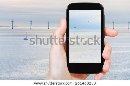 travel concept - tourist shooting photo of Middelgrunden - offshore wind farm near Copenhagen, Denmark at early morning on mobile gadget - stock photo