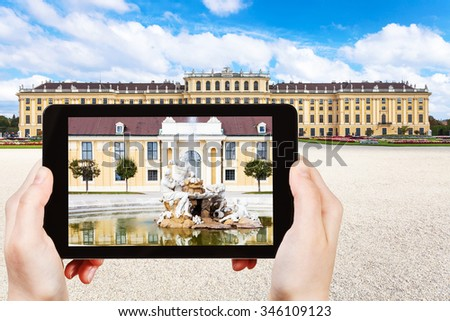 travel concept - tourist take picture of fountain near Schloss Schonbrunn palace in Vienna on tablet pv - stock photo