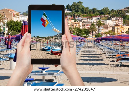 travel concept - tourist takes picture of flags Italy and Sicily at urban sand beach in resort Giardini Naxos, Sicily, Italy on tablet pc - stock photo