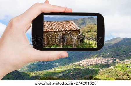 travel concept - tourist takes picture of mountain landscape with Savoca village in Sicily in spring on smartphone, Italy - stock photo