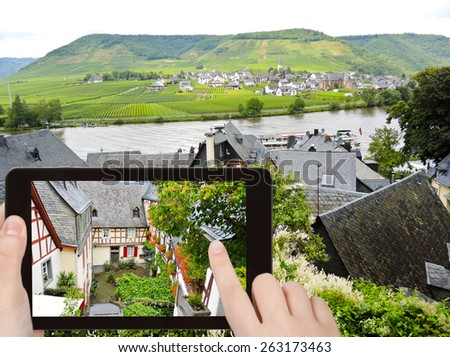 travel concept - tourist takes picture of traditional houses on narrow street in Beilstein village, Moselle region, Germany on smartphone, - stock photo