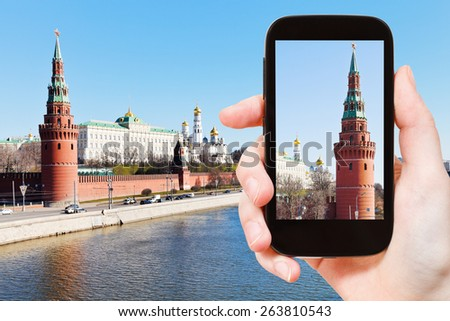 travel concept - tourist takes picture of Vodovzvodnaya Tower of Moscow Kremlin in spring day on smartphone, - stock photo