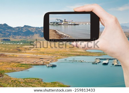 travel concept - tourist taking photo of Boulder Beach on Lake Mead on mobile gadget, Nevada, USA - stock photo