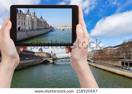 travel concept - tourist taking photo of Conciergerie palace, Pont Neuf, Pont de Notre Dame in Paris in spring on mobile gadget, France - stock photo