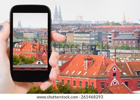 travel concept - tourist taking photo of Copenhagen city on mobile gadget, Denmark - stock photo
