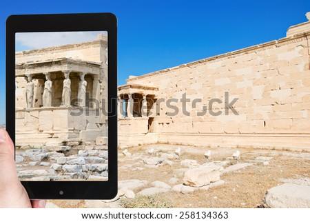 travel concept - tourist taking photo of erechtheion monument at acropolis on mobile gadget, Athens, Greece - stock photo