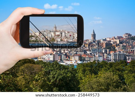 travel concept - tourist taking photo of Galata Tower in Istanbul on mobile gadget, Turkey - stock photo