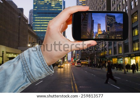 travel concept - tourist taking photo of New York City in evening on mobile gadget - stock photo