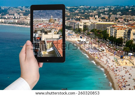 travel concept - tourist taking photo of Nice city on Azure coast, France on mobile gadget - stock photo