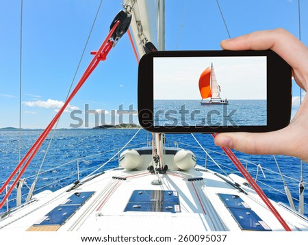 travel concept - tourist taking photo of red yacht in blue Adriatic sea, Dalmatia, Croatia on mobile gadget - stock photo