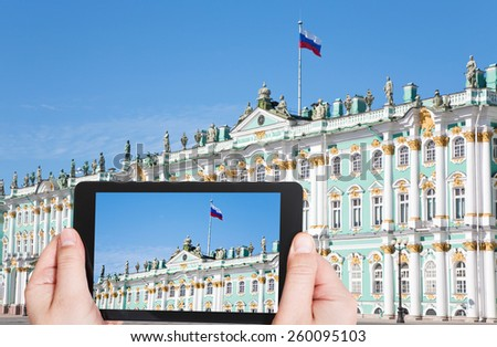 travel concept - tourist taking photo of Russian state flag on Winter Palace, St.Petersburg, Russia on mobile gadget - stock photo