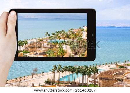 travel concept - tourist taking photo of waterfront on Dead Sea in Jordan on mobile gadget - stock photo