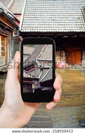 travel concept - tourist taking photo of wooden houses in rain, Bergen, Norway of on mobile gadget - stock photo