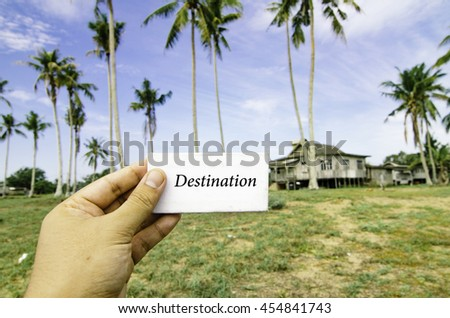 travel concept with word destination over blurred background of rural area.wooden house surrounded by coconut tree at sunny day and cloudy blue sky - stock photo