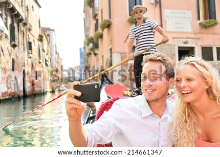 Travel couple in Venice on Gondole ride romance in boat happy on vacation holidays. Romantic young beautiful couple taking selfie photo with smartphone sailing in venetian canal in gondola. Italy. - stock photo