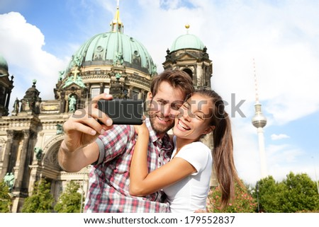 Travel couple selfie self portrait, Berlin, Germany. Happy tourists people in front of Berlin Cathedral / Berliner Dom with Fernsehturm / Berlin TV Tower in the background. Asian woman, Caucasian man. - stock photo