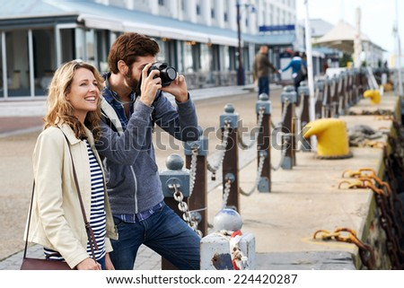 travel couple taking photos on holiday - stock photo