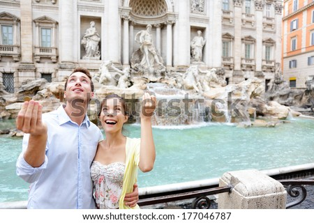 Travel couple trowing coin at Trevi Fountain, Rome, Italy for good luck. Happy young couple smiling traveling together on romantic travel vacation holiday in Europe. Asian woman, Caucasian man. - stock photo