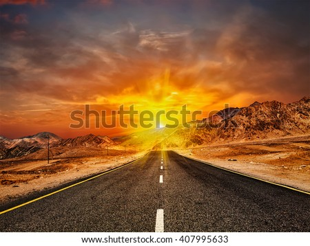 Travel forward concept background - road in Himalayas with mountains and dramatic clouds on sunset. Ladakh, Jammu and Kashmir, India - stock photo