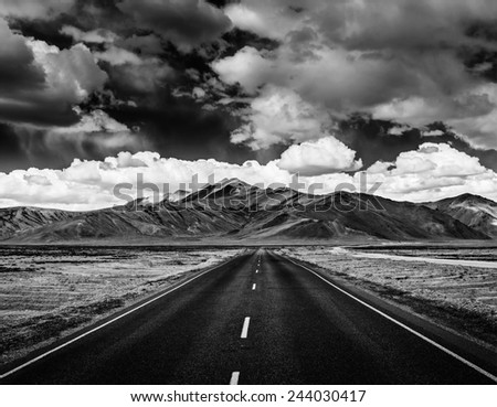 Travel forward concept background - road on plains in Himalayas with mountains and dramatic clouds. Manali-Leh road, Ladakh, Jammu and Kashmir, India. Black and white version - stock photo