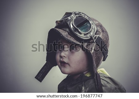 travel, fun and funny child dressed in aviator hat and goggles - stock photo