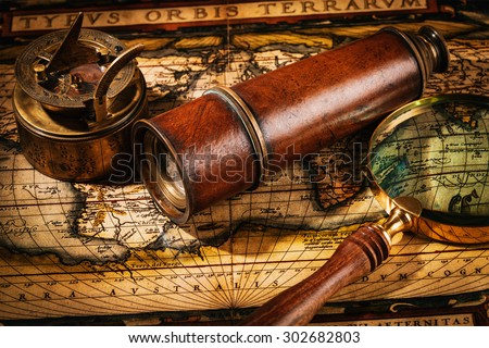Travel geography navigation concept background - old vintage retro compass with sundial, spyglass and magnifying glass on ancient world map - stock photo