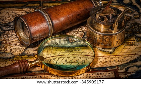 Travel geography navigation concept background - panorama of old vintage retro compass with sundial, spyglass and magnifying glass on ancient world map - stock photo