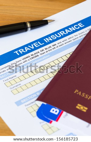 Travel insurance application form with pen and passport - stock photo