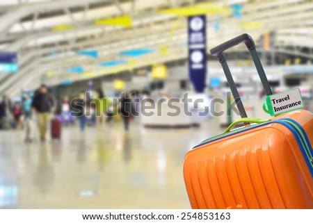 Travel Insurance. Blue suitcase with label at airport. - stock photo