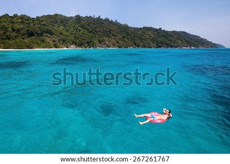 travel insurance concept, man swimming in lifebuoy on paradise beach - stock photo