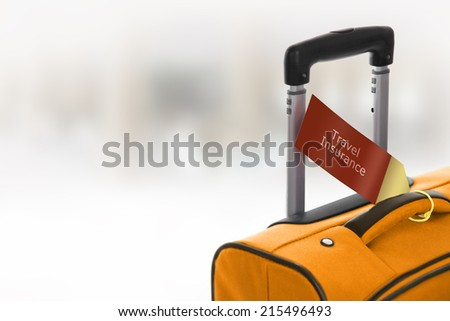 Travel Insurance. Orange suitcase with label at airport. - stock photo