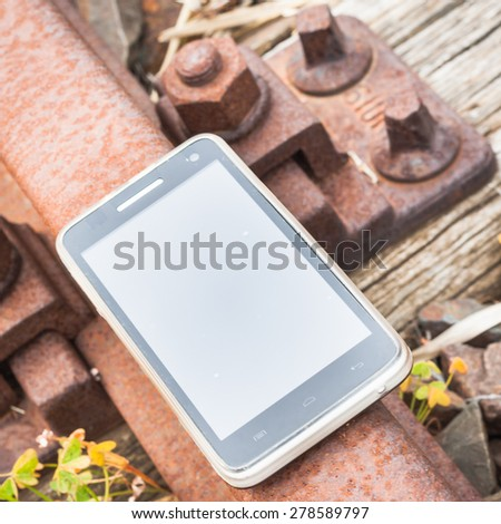 Travel on the tracks of the technology. Smartphone on rail like a metaphor. - stock photo