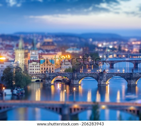 Travel Prague concept background - elevated view of bridges over Vltava river from Letna Park with tilt shift toy effect shallow depth of field. Prague, Czech Republic in twilight - stock photo