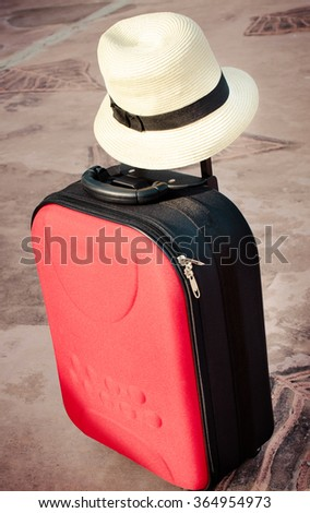 Travel red bag and straw hat, Vintage style effect image - stock photo