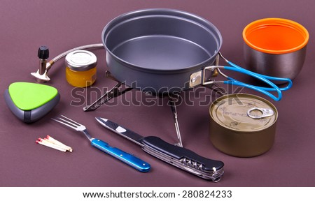 Travel set for eating. Tourist's dish kit. Various professional tools and items for outdoors cooking on brown background - stock photo
