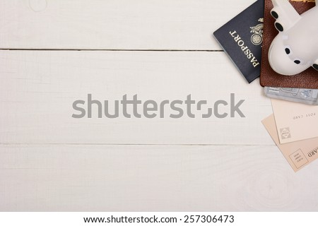 Travel Still Life on a white wood table.  Passport, toy plane, wallet with money and post cards in the upper right corner on a white wood table with copy space. - stock photo