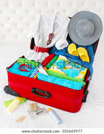 Travel suitcase packed for vacation with personal belongings. Concept. Preparation for holidays in sea resort: what to pack to the luggage. Isolated on white - stock photo
