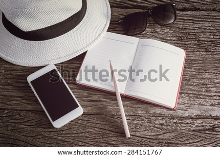 travel, summer vacation, tourism and objects concept. close up of hat, notebook, pencil, smartphone and sunglasses on wooden table. Photo retro style - stock photo