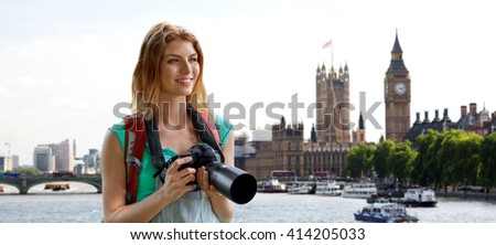 travel, tourism and people concept - happy young woman with backpack and camera photographing over london city street and big ben tower background - stock photo